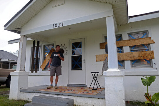 Don Wells smokes a cigarette on the porch of his boarded up home as Hurricane Delta approaches in Lake Charles