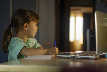 Distance online education. Little schoolgirl studies at home.