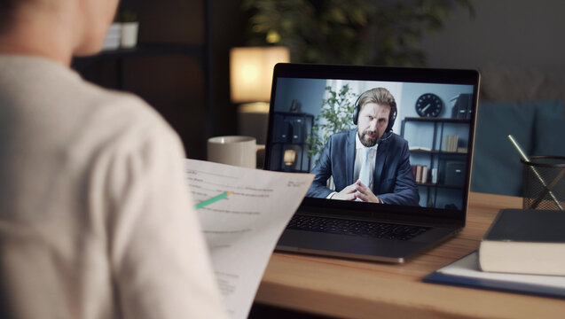 Overshoulder view of person holding papers talking to male business partner using video call