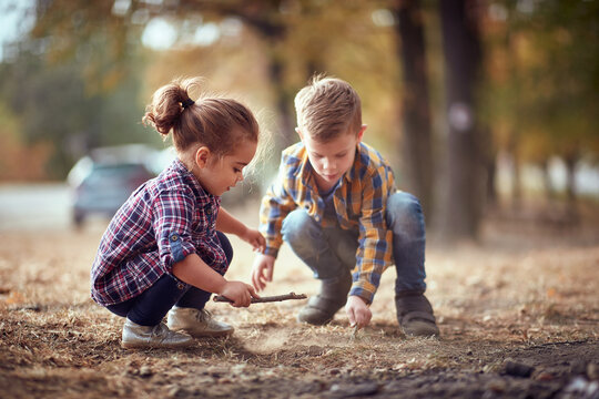 Little brother and sister playing in the dirt in the forest