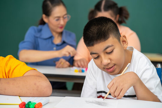 disability kid on wheelchair with Autism child in special classroom