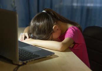 Tired child in front of the computer. Online education for kids. Tired and bored teenage girl sleeping.