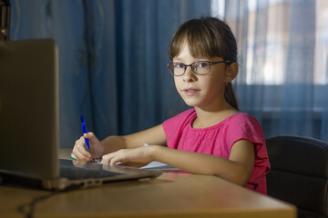 Distance online education. Adorable schoolgirl studies at home.
