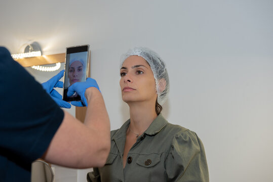 Beautician is taking photo with mobile phone of attractive young woman before treatment. Hands protected with gloves, stay safe from virus concept