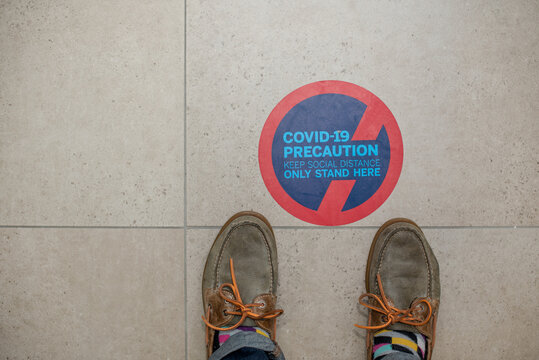 Feet standing next to social distance sign on floor