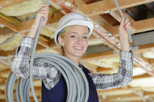 female electrician putting pipes in the ceiling