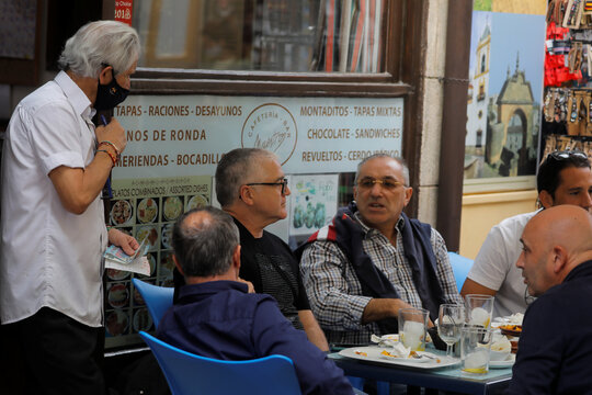 A waiter holds two 20 Euro banknotes atfer diners paid him their lunch at the terrace of the Maestro coffee bar, amid the coronavirus disease (COVID-19) outbreak, in Ronda