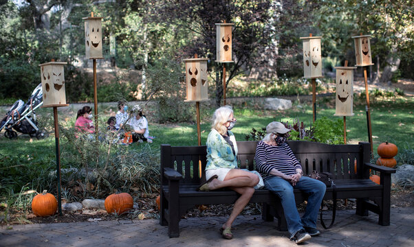 """Visitors sit by a wooden jack-o-lanterns installation during the """"Halloween at Descanso"""" event at Descanso Gardens in La Canada Flintridge"""