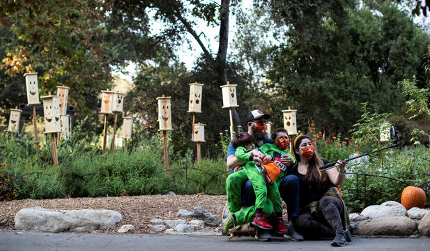 """A family wearing protective face masks takes a selfie by a wooden jack-o-lanterns installation during the """"Halloween at Descanso"""" event at Descanso Gardens in La Canada Flintridge"""