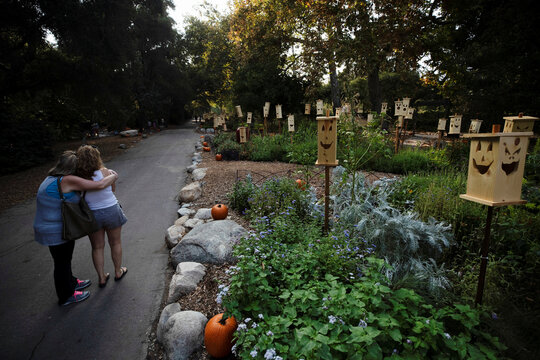 """People embrace by a wooden jack-o-lanterns installation during the """"Halloween at Descanso"""" event at Descanso Gardens in La Canada Flintridge"""