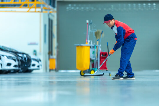 Asian worker in car mechanic repair service center cleaning using mops to roll water from the epoxy floor. Mops in the car repair service center..