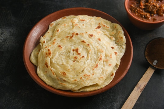 Kerala paratha porotta meat curry roti Malabar parotta barotta is Indian layered flatbread for breakfast or snack, popular street food in India. Maida or wheat flour Cooking the dough.