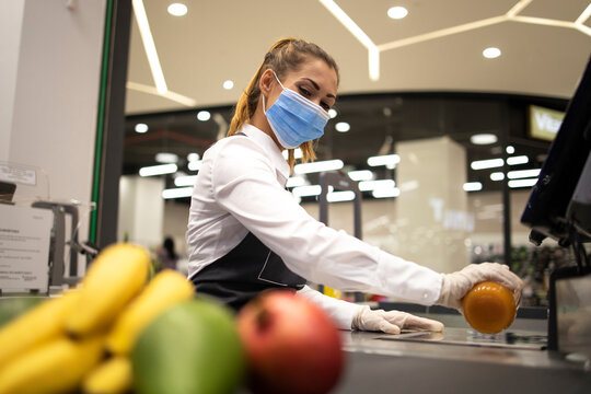 Female cashier in supermarket wearing hygienic protection mask and gloves while working risky job because of corona virus pandemic.