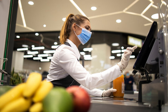 People endangered on their workplace because of corona virus. Cashier with protective hygienic mask and gloves working in supermarket and fighting against COVID-19 or corona virus pandemic.