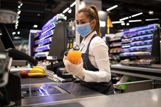 Working during covid-19 pandemic. Cashier at supermarket wearing mask and gloves fully protected against corona virus.
