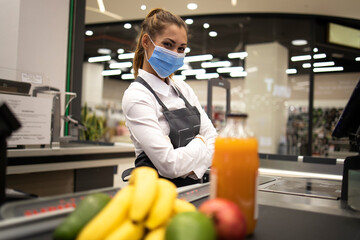 Portrait of cashier in supermarket wearing mask and gloves fully protected against corona virus....
