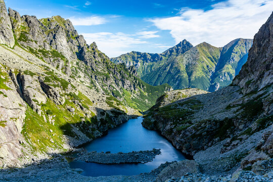 Mountain summer scenery. Shaded lake in the valley by the surrounding rock walls. In the background, the green slopes of the peaks. Tatry Mountains. Slovakia.