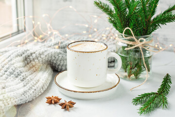 Cup of coffee, scarf and bouquet of fir tree branches. Cozy autumn or winter composition....