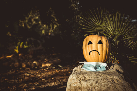 natural halloween pumpkin angry because it can not celebrate because of the coronavirus , covid 19
