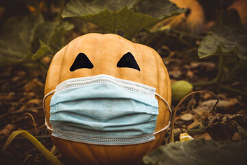 natural halloween pumpkin masked by the coronavirus pandemic, covid 19
