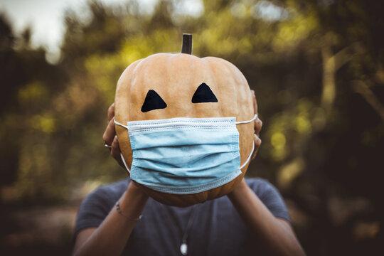 halloween 2020 pumpkin with a mask due to the covid 19 , coronavirus