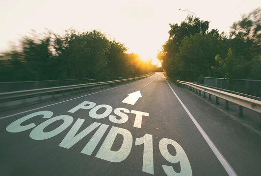 """The empty road in the forest and the text on the asphalt """"Post covid19""""."""