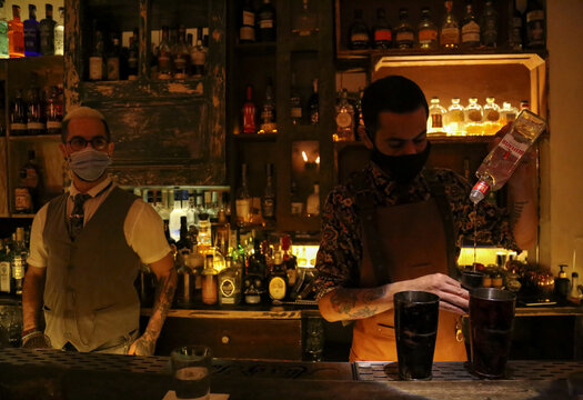 A bartender wearing a protective face mask pours Beefeater Gin at a bar in Beirut
