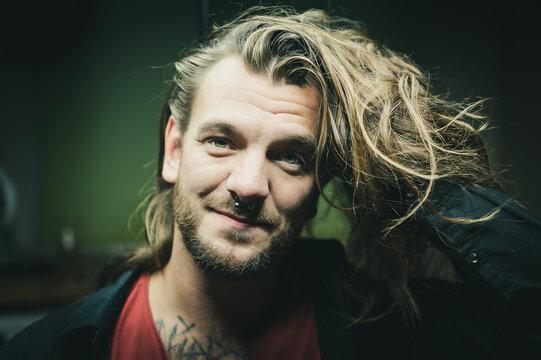 Man grabs his long hair and smiles friendly at the camera