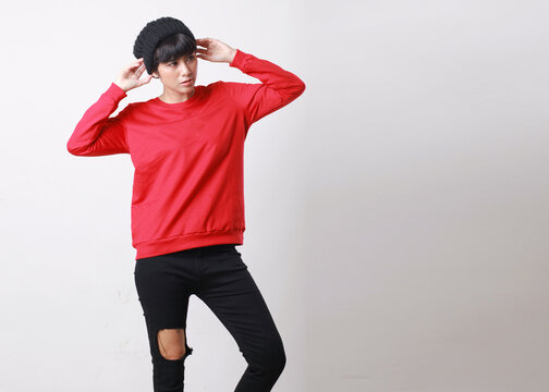 Asian model wearing beanie, red sweater and black ripped jeans standing and posing on grey background
