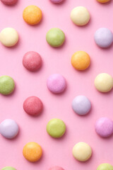 Colorful round candy sweets pattern on a pink background viewed from above. Top view