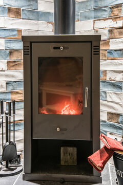 Modern wood burning stove with accessories and red gloves next to it. Wood burning stove with orange yellow flames.