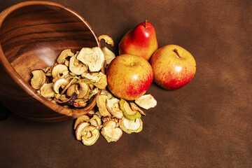 Dried apples and pears on a brown background