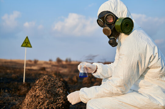 Scientist in protective suit, gas mask holding test tube with blue liquid while studying burnt grass and soil on scorched territory with biohazard sign. Concept of ecology, research and burned earth