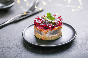 Shuba salad. Russian layered salad with beet, potato, carrot, pickled herring and mayonnaise for Christmas dinner