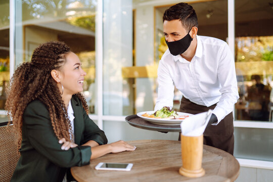 Young waiter in  protective face mask and gloves while bringing food to a customer in cafe during coronavirus epidemic. Covid- 2019.
