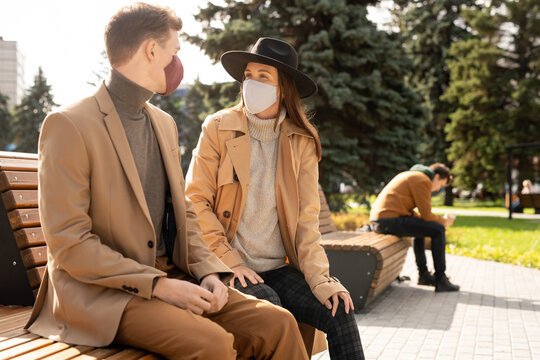 Happy young stylish couple in protective masks relaxing on bench in park