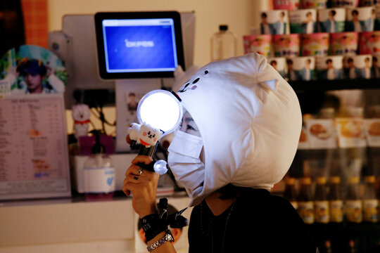 A fan of K-pop idol boy band BTS watches a live streaming online concert, wearing a protective mask at a cafe, in Seoul