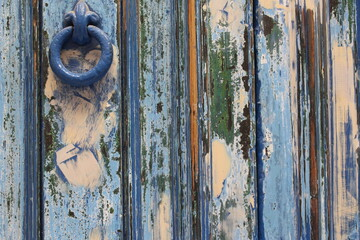 A close up photograph of old paint texture in various colours, on an old wooden door