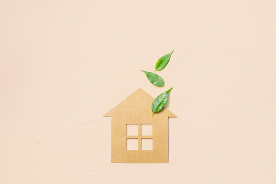 House made of craft paper and green leaves of a plant on a light background. Eco-friendly home concept, healthy lifestyle, zero waste.