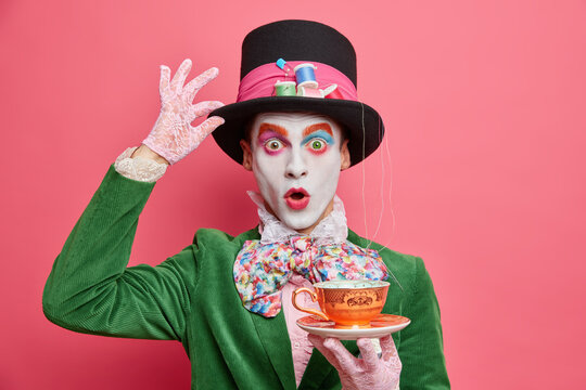 Surprised male hatter wears gentlemans clothes holds cup of hot tea pretends to come from wonderland wears vivid makeup celebrates halloween on costume party poses indoor alone. Body painting