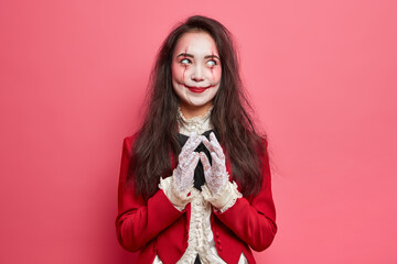 Photo sur Plexiglas Dinosaurs Scary brunette woman with zombie eyes and bloody scars dressed in halloween costume steepls fingers and has evil plan isolated over pink background. Horrible scary female on masquerade party