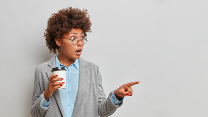 Photo sur Plexiglas Dinosaurs Stunned female lawyer with greatly surprised expression points away on copy space drinks takeaway coffee and wears formal clothes indicates something isolated on grey background. Check this out