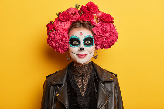 Cheerful female with artistic halloween makeup wears traditional attire for mexican day of death to honor dead relatives has spooky image poses against yellow background. Costume masquerade.