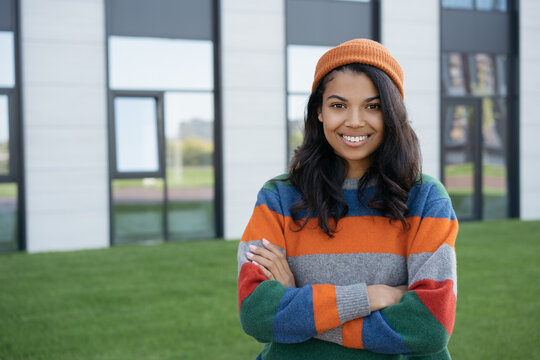 Portrait of young successful university  student with arms crossed posing for pictures. Beautiful smiling African American woman looking at camera, standing outdoors