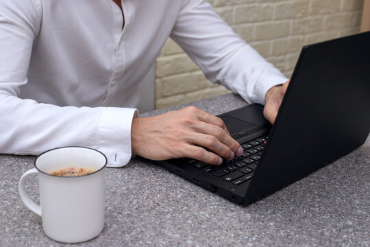 A young man of 30 years old works at a computer. Remote work, training, online.