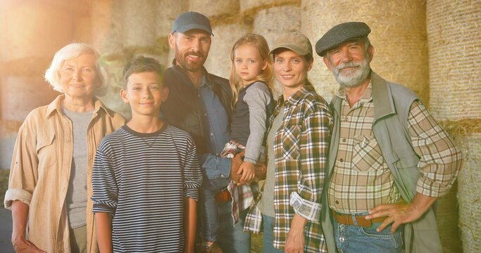 Portrait of happy Caucasian family of three generations standing outdoor at hay stocks and smiling to camera. Old parents with children and grandchildren in countryside. Farmers at farm. Summer.