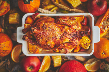 Festive chicken baked by Thanksgiving on white owen plate and a harvest of seasonal vegetables