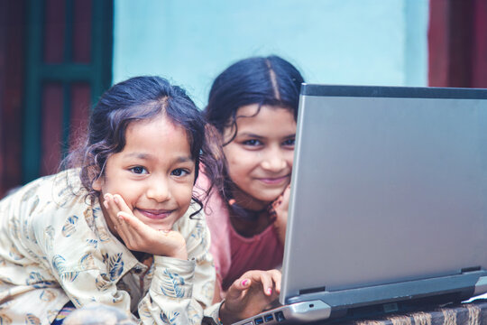 Indian village girls operating laptop computer system seating at home corridor
