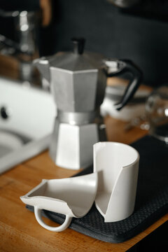 Broken white ceramic coffee mug on a wooden table in the kitchen. Accident, brokenness, negligence.