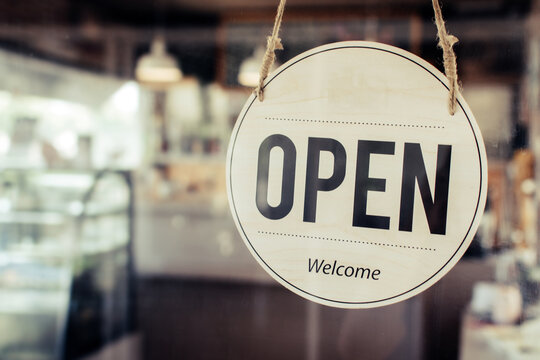 Open. coffee cafe shop text on vintage sign board hanging on glass door in modern cafe shop reopen after coronavirus quarantine is over in restaurant ready to service, small business owner concept